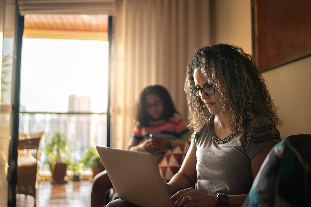 Woman on laptop looking up life insurance options