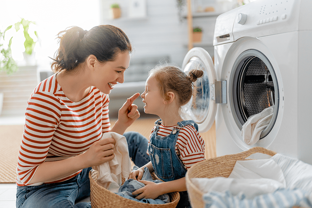 Mother and daughter doing laundry with natural products